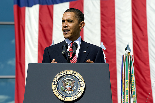 President Obama with background of broad red and white stripes of U.S. flag (credit: keyword suggest.org)